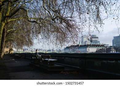 """""""London, England""""; February 6 2019: Man in formal wear sitting on a bench with a book on his hands while staring at the river Thames on a sunny winter morning."""