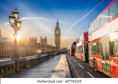 London, England - The iconic Big Ben and the Houses of Parliament with lamp post and famous red double-decker buses on Westminster bridge at sunset with blue sky