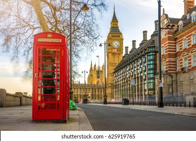 London, England - The iconic british old red telephone box with the Big Ben at background in the center of London at sunset