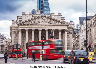 London, England - Iconic red double decker buses on the move and black london taxis with the Royal Exchange building