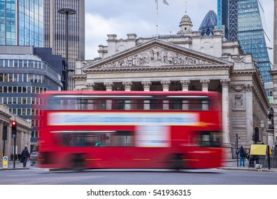 London, England - Iconic red double decker bus on the move with the Royal Exchange building at background