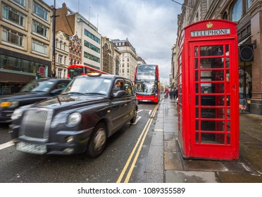 London, England - Iconic red double-decker buses on the move with traditional red telephone box in the center of London at daytime