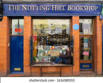 London, England - january 2020: woman sitting in front of the famous Notting Hill bookshop, located at 13 Blenheim Crescent