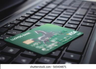 LONDON, ENGLAND - JANUARY 21, 2017: Green Visa, Lloyds bank card, on a black laptop computer keyboard.
