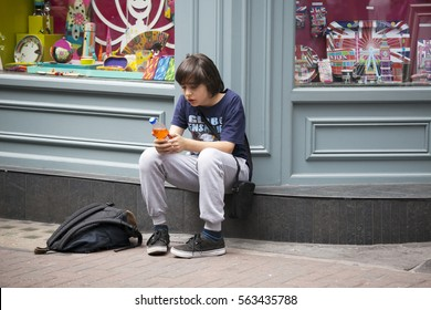 LONDON, ENGLAND - JULY 12, 2016 Teenager sitting on the sidewalk near the store, waiting for friends