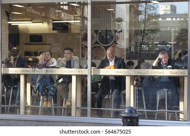 LONDON, ENGLAND - JULY 12, 2016 Bored people sitting in cafe, looking at the street