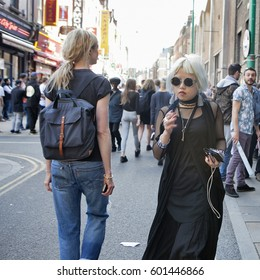 LONDON, ENGLAND - JULY 12, 2016 fashionably dressed blond girl in sunglasses in a black tunic walking along the Brickline