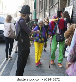 LONDON, ENGLAND - JULY 12, 2016 An elderly couple very brightly and fashionably dressed are walking along bricklane.