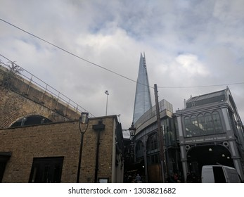 LONDON, ENGLAND - JULY 12, 2018: Buildings of Borough Market thronged with tourists and shoppers, with glimpse the famous The Shard Tower in the distance . A fashionable district of London, UK