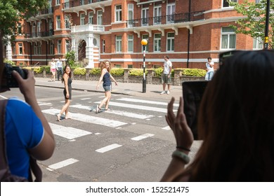 LONDON, ENGLAND - JULY 17: Tourists photograph as people walk the pedestrian crossing in famous Abbey road as tyhe beatles did in 1960's on Abbey Road in London July 17, 2013.