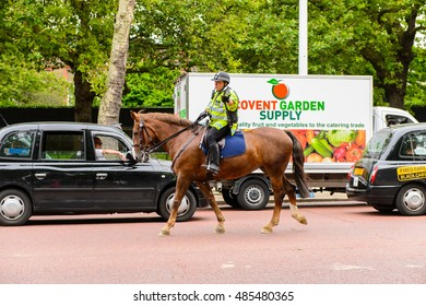 LONDON, ENGLAND -  JULY 20, 2016: Horse police with the Queen's Guard heading to the Buckingham Palace for the changing of guard proccess.