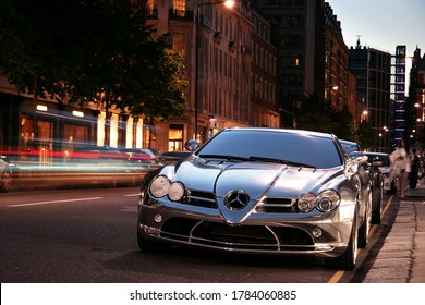 London, England - July 2011: A chrome Mercedes-Benz SLR McLaren (modified by Brabus) parking on Sloane Street at night, with traffic in motion next to it.