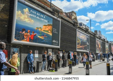 LONDON, ENGLAND - JULY 2018: Advertising posters on a wall outside London Paddington railway station with a crowd of people standing on the approach road