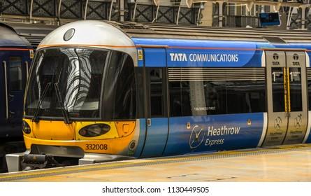 LONDON, ENGLAND - JULY 2018: Heathrow Express electric train alongside a platform at London Paddington Station.