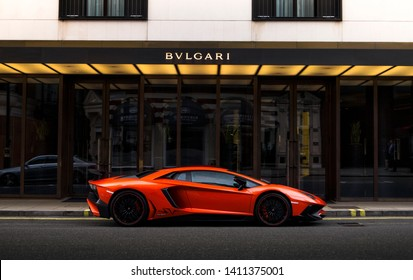 London, England - July 2018: side view of an orange Lamborghini Aventador SV supercar, parked besides a luxury hotel in Knightsbridge area of central London.