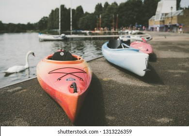 London, England - July 2018 : Three kayaks on the shore of a small lake in summer in Wimbledon Park