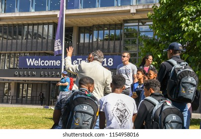 LONDON, ENGLAND - JULY 2018: Tour guide explaining historical facts to a group of young tourists in Westminster. The QE2 Centre is in the background.