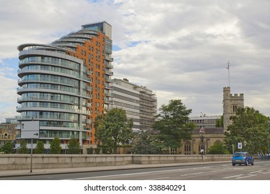 LONDON, ENGLAND - JULY 27, 2012: Modern building and ancient church seen from the Putney bridge