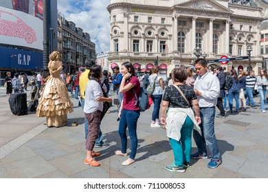 LONDON, ENGLAND - JUNE 09, 2017: Living statue and unknown people at Piccadilly Circus in London, UK