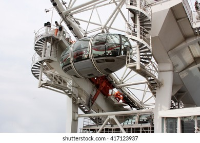 LONDON, ENGLAND - JUNE 12 2015: The London Eye is a giant Ferris wheel on the South Bank of the River Thames in London. Also known as the Millennium Wheel. The capsule has a Coca-Cola logo.