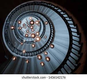 London,  England, June 2019: The Cecil Brewer spiral staircase hypnotically whirls upward at Heal's London furniture store with colorful effects and multiple lamps
