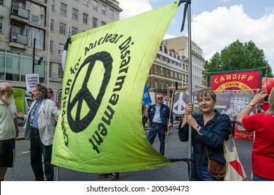 LONDON, ENGLAND - JUNE 21, 2014:  Campaign for Nuclear Disarmament General Secretary Kate Hudson, holding the group's banner during a march through London campaigning against the Coalition Government.
