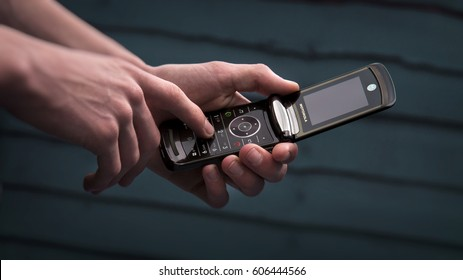 London, England - June 24, 2014: Person Using a Motorola Razr Mobile Phone, First introduced in 2004.
