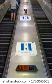 LONDON, ENGLAND - JUNE 8, 2020:  Young man observing the 6 step separation guidance on a London Underground Escalator during the COVID-19 pandemic