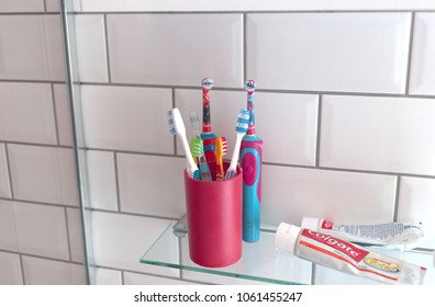 LONDON, ENGLAND - MAR 29, 2018: A variety of multi branded manual and electric toothbrushes, alongside tubes of Colgate toothpaste, in a bathroom setting.