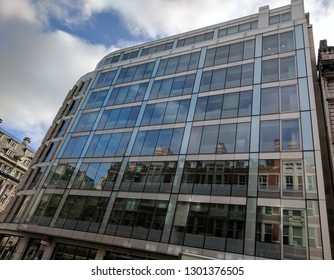 LONDON, ENGLAND - MARCH 1, 2018: The Exterior and sign of a modern steel and glass Sainsbury's seven-eleven convenience store in Holburn/Bloomsbury, London, with reflections of surrounding buildings