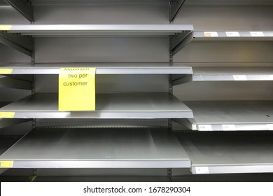 """London, England - March 16 2020 - Empty shelves in a Morrison's Supermarket in Morrison's on Walworth Road, Southwark, with a sign that says """"Maximum two per customer"""".  Image has copy space."""