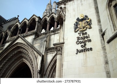 London, England - March 17, 2015: Part of the exterior facade of the Royal Courts of Justice in London, England showing the coat of arms of the courts and architectural details