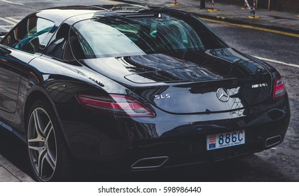 LONDON, ENGLAND - MARCH 1st, 2017: Black Mercedes-Benz SLS AMG parked on a road in London, UK, view from behind.