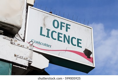 LONDON, ENGLAND - MARCH 1st, 2017: OFF LICENCE, Costcutter broken sign with a blue sky in the background, Harrow, London.