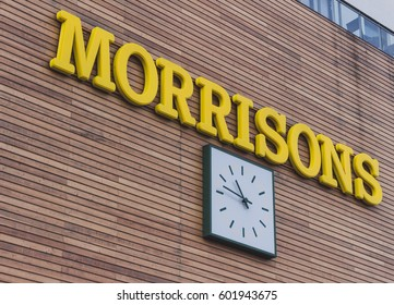 LONDON, ENGLAND - MARCH 1st, 2017: Exterior of the Morrisons supermarket, sign yellow logo next to large white clock on the wall.