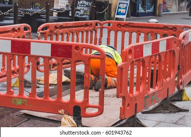 LONDON, ENGLAND - MARCH 1st, 2017: Worker working on his knees, on the main street, broadway, public footpath.