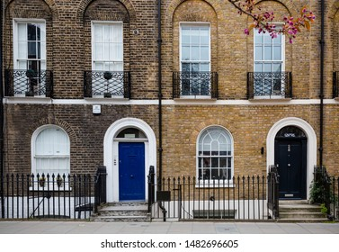 London, England, March 2019: central London with traditional red brick Victorian buildings with charming entrances and facade