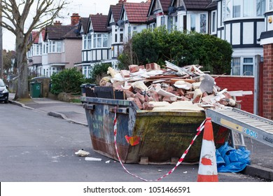 LONDON, ENGLAND - MARCH 6, 2017: Skip full of bricks and other rubbish on the side of the street.
