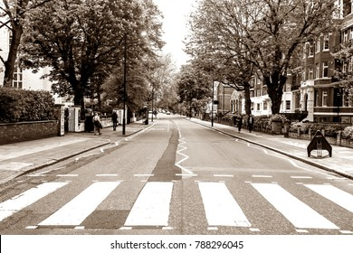LONDON, ENGLAND - MAY 10, 2012 : The famous scenery of zebra crossing at Abbey Road made famous by the 1969 Beatles album cover. Sepia color.