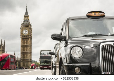 LONDON, ENGLAND - MAY 21, 2016: London's taxi and red buses front of big ben on a  cloudy day, selective focus