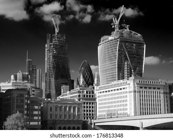 """LONDON, ENGLAND - MAY 25: the """"Gherkin"""" between two skyscrapers under construction in the City of London on May 25, 2013."""