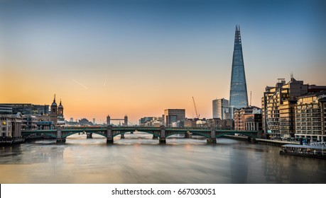 London, England. May 26, 2017. View from the Millennium Bridge showing The Shard and Tower Bridge during sunrise.