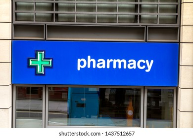 London, England - May 6, 2019: Pharmacy store entrance and sign pharmacy in downtown city during daytime