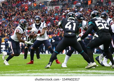 LONDON, ENGLAND - NOVEMBER 03 2019: Houston Texan's quarterback, Deshaun Watson (4) hands off to running back, Carlos Hyde (23) during the NFL game between Houston Texans and Jacksonville Jaguars