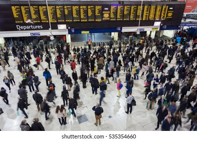 LONDON, ENGLAND - OCT 19, 2016 : Many people in front of time board in rush hour at Waterloo train station, London, England.Waterloo station, a central London railway terminus.