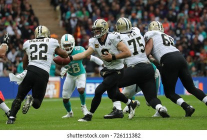 LONDON, ENGLAND - OCTOBER 01 2017: quarterback Drew Brees (9) hands off to running back Mark Ingram (22) during the NFL match between the Miami Dolphins and the New Orleans Saints at Wembley Stadium
