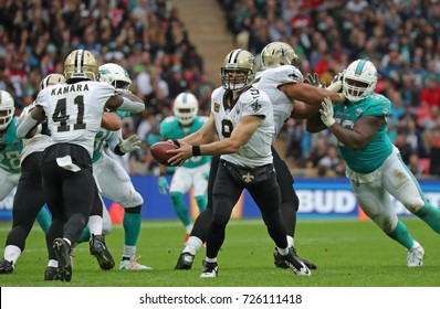 LONDON, ENGLAND - OCTOBER 01 2017: New Orleans Saints quarterback Drew Brees (9) hands off during the NFL match between the Miami Dolphins and the New Orleans Saints at Wembley Stadium