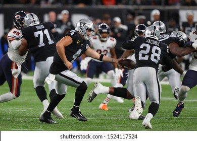 LONDON, ENGLAND - OCTOBER 06 2019: Quarterback Derek Carr of The Oakland Raiders hands off to Running-back Josh Jacobs during the NFL game between Chicago Bears and Oakland Raiders