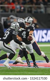 LONDON, ENGLAND - OCTOBER 06 2019: Quarterback Chase Daniel of The Chicago Bears hands off to Running-back Josh Jacobs during the NFL game between Chicago Bears and Oakland Raiders