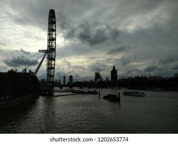 London, England - October 11 2018: changing London city skyline across the River Thames to Westminster houses of parliament with Millenium wheel view from  southbank  Waterloo bridge with stormy sky
